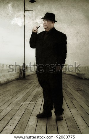 Fifties Detective Wearing Hat And Suit Smoking A Pipe On A Olden Wooden Pier While Piecing Together Clues To Solve A Mystery - stock photo