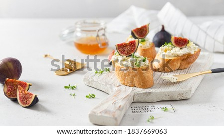 Fig, cream cheese and honey sandwiches. Canape or crostini with toasted baguette, cream cheese, figs and microgreen on a wooden board on white background. Italian recipe menu. Side view