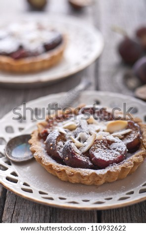Fig tart with almonds and sugar on old wood table - stock photo
