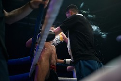 Fighter are resting after round. The coach reassures and calm down the boxer in the ring with water and sponge
