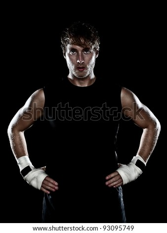 Fighter boxer standing staring strong on black background. Young masculine caucasian male athlete in his 20s.