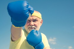 Fighter. Boxer with boxing glove. Senior man in gloves beats punching bag. Boxing. Older man boxing. I love boxing. Senior cool man fighting
