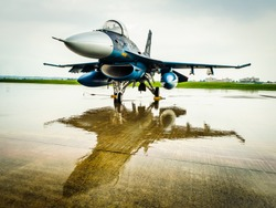 Fighter jet from Japan Air Self Defense Force on display and reflected on flight line after heavy rain