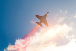Fighter jet planes fly and leave behind a smoke trail, clouds sun glare