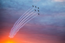 Fighter jets doing demonstrations at one air show organized by international airport from Timisoara. Sunset time.