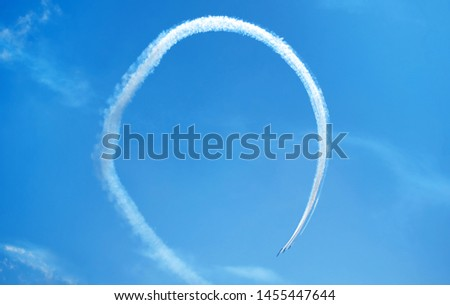 Photo of  Fighter planes contrails in loop performing fly loopings or looping in the sky forming closing loop in formation in Spain, Murcia, 2019.  Exhibition of air force. Smoke trail or contrail plane loop.