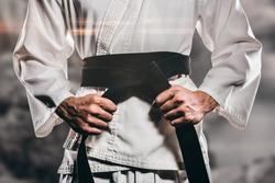 Fighter tightening karate belt against rock crashing down from cliff