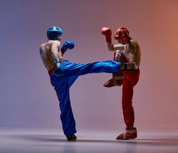 Fighting males in boxing gloves training kicking in red light in studio, martial arts workout