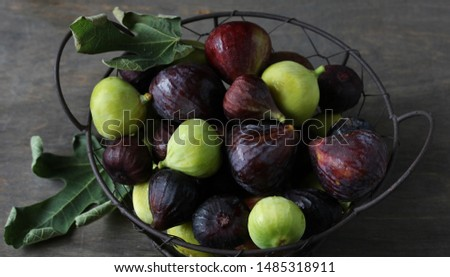 figs Different sorts  in a basket on a dark background. Large, small purple figs and white figs #1485318911