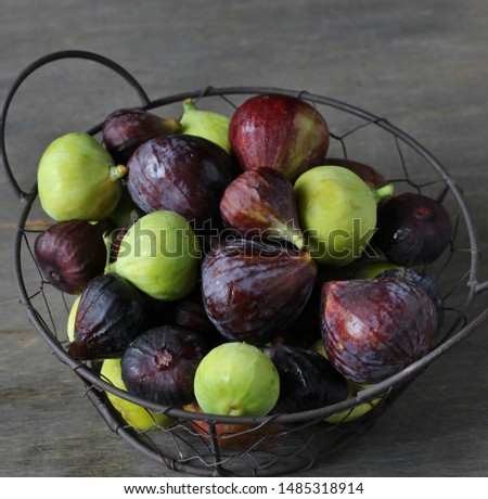 figs Different sorts  in a basket on a dark background. Large, small purple figs and white figs #1485318914