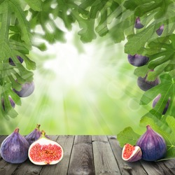 Figs fruit on summer background with green leaves and gray empty wooden board with copy space