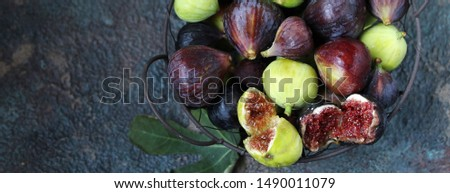 figs in a basket on a dark background. Large, small purple figs and white figs #1490011079