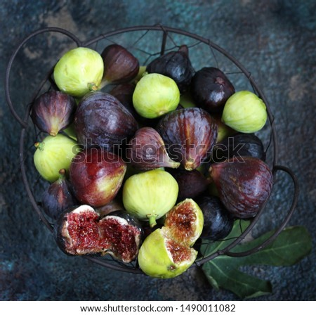 figs in a basket on a dark background. Large, small purple figs and white figs #1490011082
