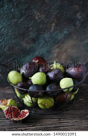 figs in a basket on a dark background. Large, small purple figs and white figs #1490011091