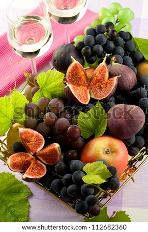 Figs with leaves, apples and dark grapes  in a bowl and  two white  wine glasses