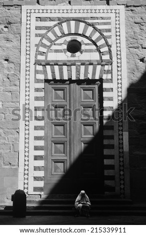 Figure in white sitting and holding bread, in front of church doors, which are in half shadow, no recognizable person, Black and White photo, small amount of noise may occur