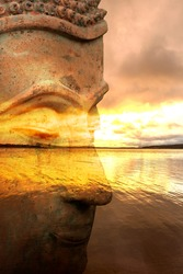 Figure of a Buddha with a lake at sunrise in the background, Spain