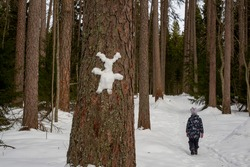 Figure of a hare made of snow on a tree. People in the forest. Lindulovskaya grove