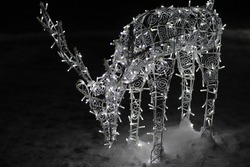 Figure of a New Year's deer in the park. Christmas deer. The glowing figure of a deer. Christmas garland and decorations