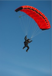 Figure of a parachutist with a bright red parachute against a blue sky.