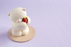 Figure of a polar bear with a gift made of chocolate on a wooden backing. Christmas gift. Selective focus.