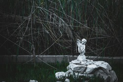 Figure of a stone angel, in a sad, melancholic and decadent environment.