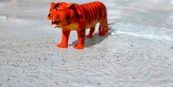 figure of a toy tiger orange close-up in the summer against the background of a summer water park selective focus.