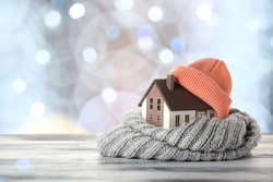 Figure of house and warm clothes on table against blurred lights. Concept of heating season