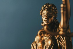 Figure of Justitia or Justice with a blindfold signifying the fair application of the law without bias in a close up view over grey and copy space in a conceptual image