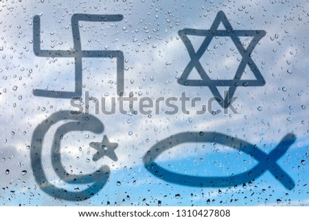 Figure of the four religious symbols - Christianity, Judaism, Hinduism and Islam on wet glass. Glass window with raindrops against the blue sky. The concept of the basic religions of the world. #1310427808