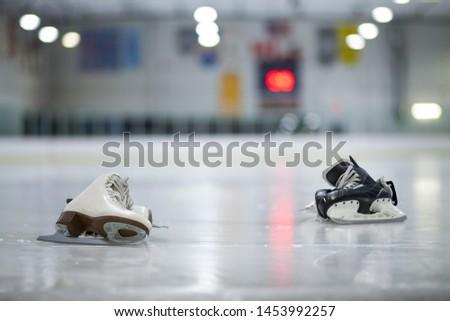Figure Skates and Hockey Skates on Ice Rink #1453992257