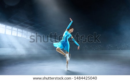 Figure skating couple in professional ice arena.