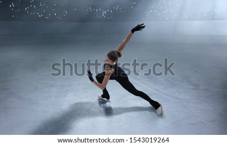 Photo of  Figure skating girl in ice arena.