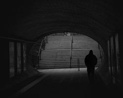 Figure walking through dark underpass