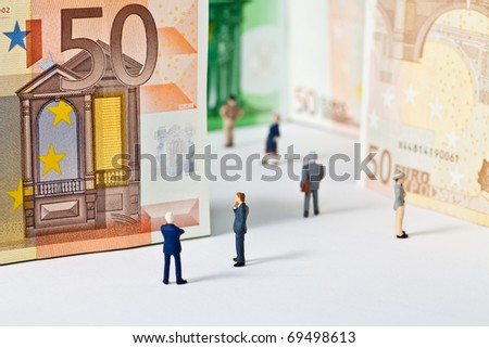 Figures are standing in front of bank notes