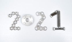 Figures 2021 from fasteners - stainless metal nuts, spacer, washers, bolts and flange on a white wooden table. Technical topics of new year day. The view from the top.
