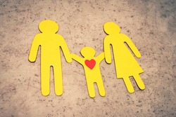 Figures of people cut out of paper. The family stands in a line and holds hands. The child loves his parents. Yellow silhouettes of a man, woman, and boy.