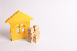 Figures of people stand near a wooden house on a white background. A young family is standing near their house. The concept of buying a home. The property. Family happiness. Unit of society.