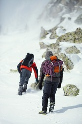 Figures of two climbers in the mountains during a winter ascent in a snow storm, rear view, close-up.