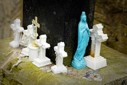 Figures of white crosses, with Jesus Christ, and the Virgin Mary under a large cross in the cemetery.