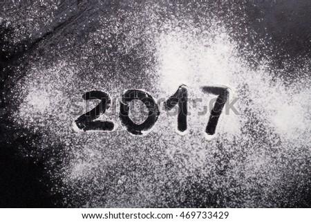 Figures 2017 on flour spilling on black metal background. #469733429