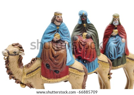 figures representing the three kings in a nativity scene on white background