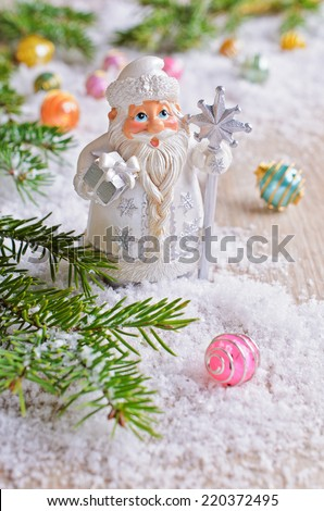 Figurine decorative Santa Claus is on the white snow in the background with fir branches and bright balls