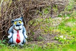 Figurine for garden decoration. Gray wolf in a red tie under a bush in a spring garden.