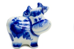 Figurine of a cow. ceramics porcelain. Folk crafts Gzhel, Small size. Macro photography. isolated on white background