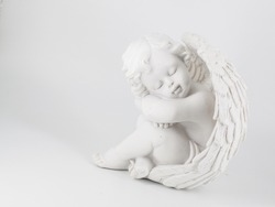 figurine of a small, white, ceramic cherub sitting on the floor with arms folded over its knees, with a pale grey background.
