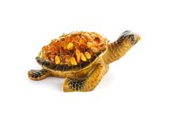 Figurine of a turtle on a white background with amber stones on the shell.