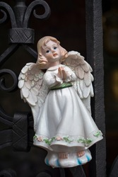 Figurine of an angel in a white dress. Decorative figure on a metal railings background. Statuette. Macro photography of isolated figurine of an angel hanging on the railings..