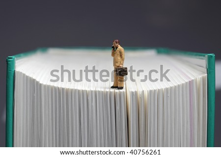 Figurine of businessman with handy standing on book, closeup
