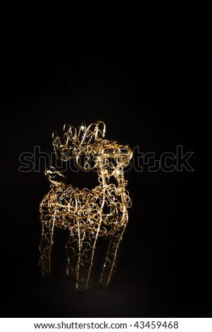 Stock Photo Figurine of christmas deer sparkling on black background
